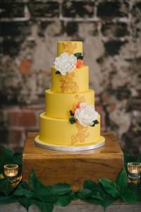 Hand on sweet yellow wedding cake