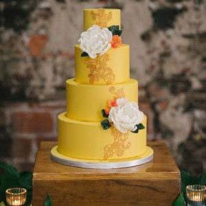 Hand on sweet yellow wedding cake